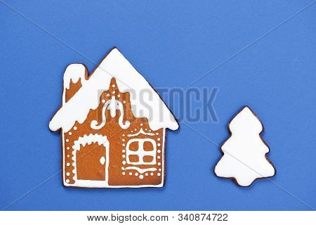 The Hand-made Eatable Gingerbread House And New Year Tree On Blue Background