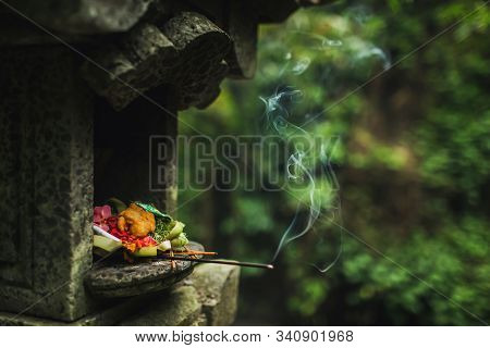 Traditional Balinese Canang Sari Offerings To Gods And Spirits With Flowers, Food And Smoky Aromatic