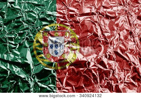 Portugal flag depicted in paint colors on shiny crumpled aluminium foil closeup. Textured banner on rough background poster
