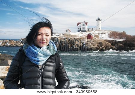 A Chinese Woman Traveling In America With The Cape Neddick Nubble Lighthouse In The Back Ground In C