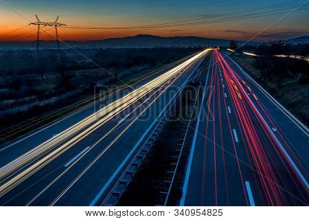 Cars Light Trails On A Straight Highway At Sunset. Night Traffic Trails, Motion Blur, Night City Roa