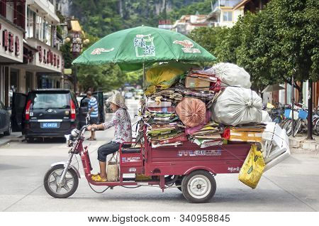 Yangshuo, China - Aug 10, 2013 - Small Truck Overloaded With Cardboard And Bags Of Plastic Bottles I