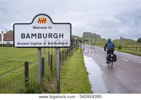 Northumberland, England - June 17, 2016 - Male Cyclist Heading Towards Bamburgh Castle, Northumberla