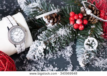 White Wristwatch With Swarovski Crystals On A Pillow And Diamond Bangles Next To Christmas Decoratio