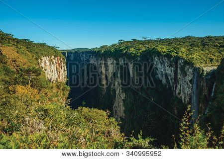 Itaimbezinho Canyon With Waterfall Coming From Rocky Cliffs In A Flat Plateau Covered By Forest Near