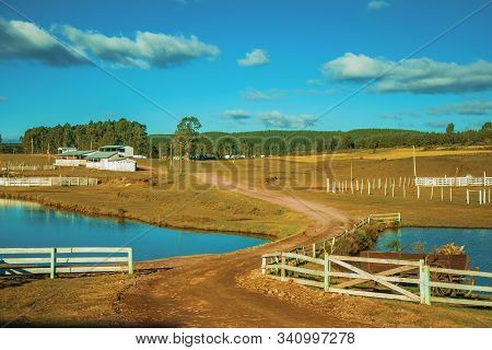 Farm With Fences, Livestock Sheds And Lake On Landscape Of Rural Lowlands Called Pampas At Cambara D