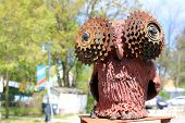 Red clay sculpture of an owl, using some industrial metal parts for the eyes. poster