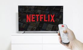 Ufa, Russia - Jule 7, 2019: Table With Popcorn Bottle And Netflix Logo On Smartphone. Netflix Is A G