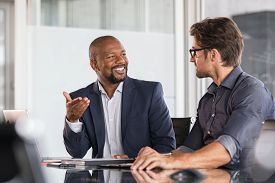 Two happy business colleagues at meeting in modern office interior. Successful african boss in a conversation with young employee in boardroom. Marketing team of two businessmen discussing strategy.