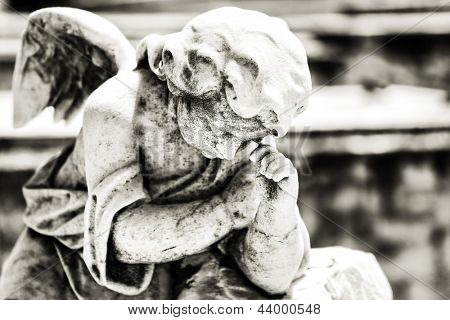 Black and white vintage image of a sad mourning angel on a cemetery with a diffused background