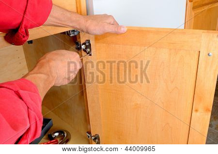 Closeup of a installers hands attaching a hinge a kitchen cabinet.