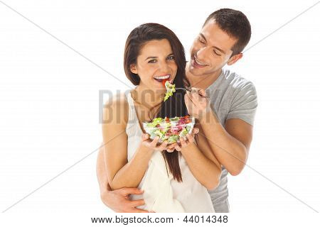 Happy Couple Eating Salad Together On A White Background
