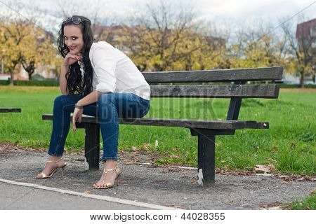 Young Woman Sitting On The Bench