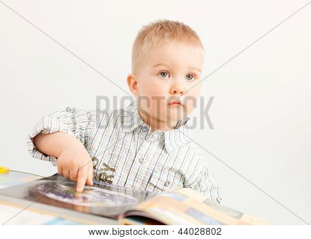 curious baby boy studying wiht the boock