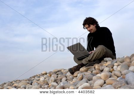 Young Man With Laptop Computer In The Outdoors