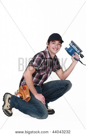 Young man holding a sander