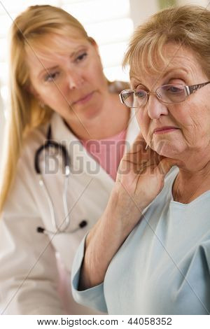 Melancholy Senior Adult Woman Being Consoled by Female Doctor or Nurse.