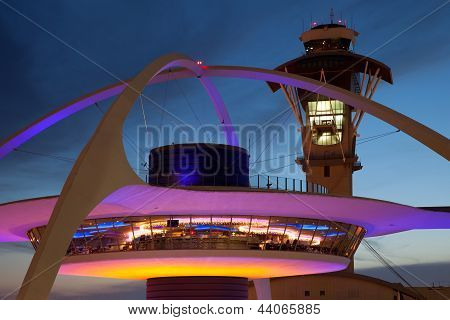 Theme Building and tower of Los Angeles International Airport at dusk poster