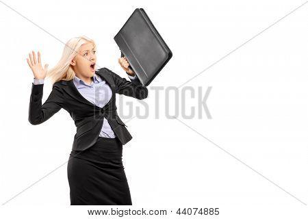Scared young businesswoman protecting with briefcase and gesturing fear isolated on white background