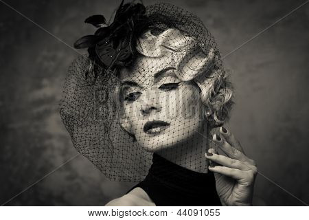 Monochrome picture of  elegant blond retro woman   wearing little hat with veil