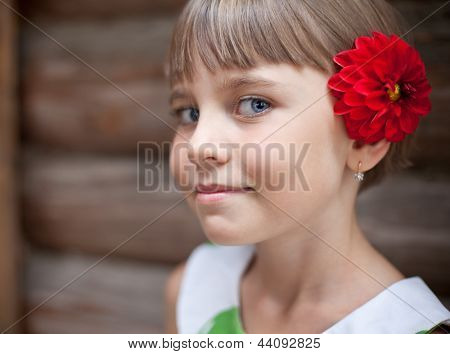 Seven-year Old Girl With A Red Flower In Her Hair