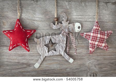 Wooden christmas deer and red stars on wooden background