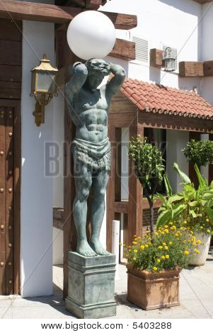Statue Of A Man Carrying Lamp