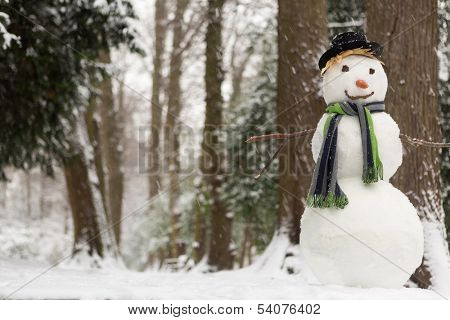 Large snowman standing in the park while it's snowing