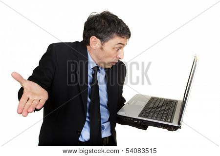 Businessman shrugging his shoulders and gesturing in disbelief or indifference as he reads his handheld laptop screen with a look of stupefied amazement