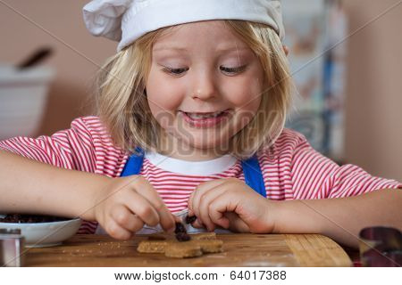Cute Smiling Boy Putting Raisins On Gingerbread
