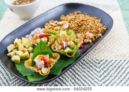 Leaf wrapped bite size appetizer grated coconut ginger shallots peanuts dried shrimps lime chillies and edible tree leaves Miang Kum Traditional Thai food. poster