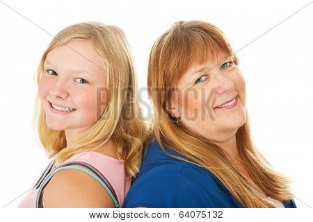 Blond mother and beautiful teenage daughter standing back to back.  Isolated on white.