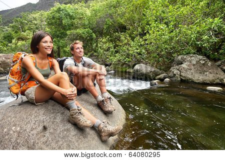 Hiking couple of hikers in outdoor activity wearing backpacks relaxing. Woman and man hiker looking with smiling happy. Healthy lifestyle image from Iao Valley State Park, Wailuku, Maui, Hawaii, USA.
