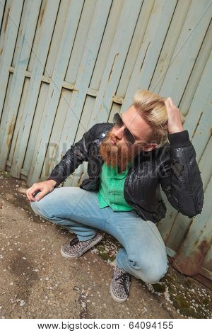 young casual bearded man crouching and passing his hand through his hair while looking away from the camera