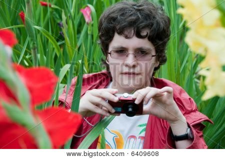 Girl With Camera In The Flowerbed