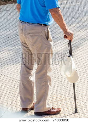 a tourist with a cane and a hat for sun protection