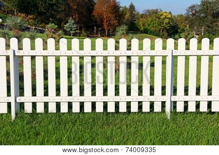 White Fence On Green Grass.