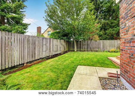 Backyard With Wooden Fence And Walkway