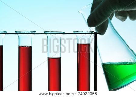 Chemical laboratory concept. Hand in glove with Erlenmeyer flask behind rack of test tubes, blue light