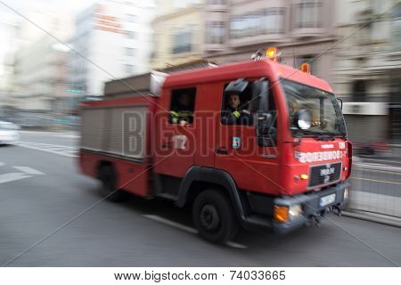 MADRID, SPAIN - OCTOBER 10, 2014: A fire truck speeding through the streets of Madrid. Due to Spanish law, only police use blue lights and ambulances and fire engines have to use amber lights.