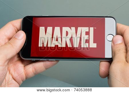 Hands Holding Apple Iphone 6 With Logo Of Brand Marvel