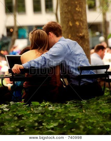 Couple In Park With Wireless Computer.
