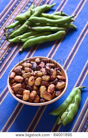 Roasted broad beans (lat. Vicia faba) eaten as snack in Bolivia in bowl with fresh broad bean pods on the side and in the back on blue fabric photographed with natural light (Selective Focus Focus one third into the roasted beans) poster