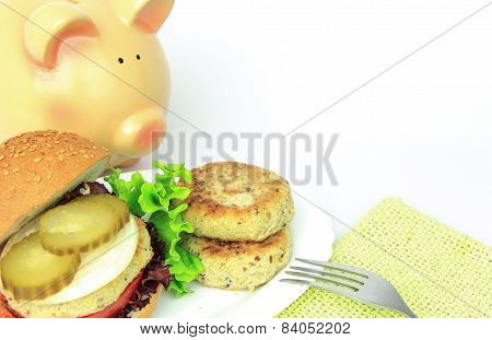 Vegan sea patties and burger on plate with piggy bank conceptual poster