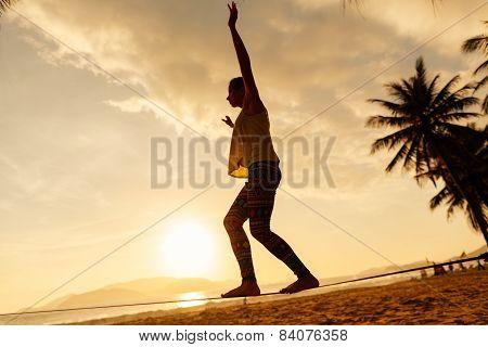 Teenage Girl  Balancing On Slackline Silhouette On The Beach