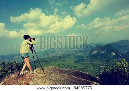woman hiker photographer taking photo at mountain peak cliff