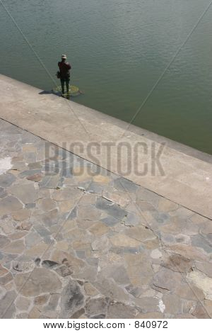 Statue Of Man Fishing In Lake