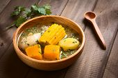 Traditional Chilean Cazuela de Pollo (or Cazuela de Ave) soup made of chicken sweetcorn pumpkin and potato seasoned with fresh coriander served in wooden bowl photographed on wood with natural light (Selective Focus Focus one third into the soup) poster