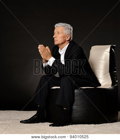 Praying mature businessman sitting in chair
