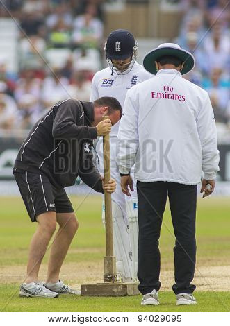 NOTTINGHAM, ENGLAND - July 14, 2013: Ground staff repair the pitch during day five of the first Investec Ashes Test match at Trent Bridge Cricket Ground on July 14, 2013 in Nottingham, England.